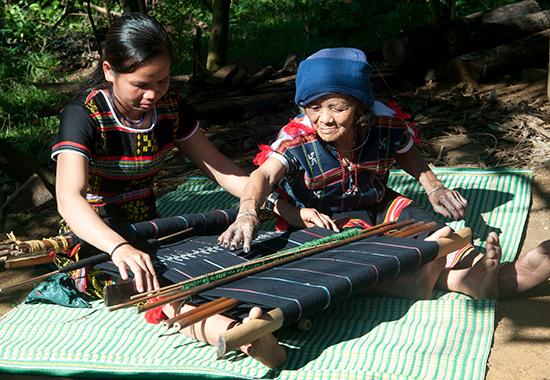 Cụ bà nghệ nhân Cơ Tu truyền dạy kỹ thuật dệt hoa văn gợn sóng cho thợ dệt trẻ tại làng dệt Công Dồn. Ảnh: T.VỊNH