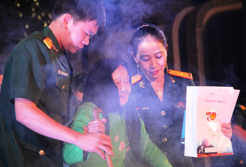 Các chiến sĩ dìu mẹ trở về hàng ghế sau khi nhận quà tri ân. Ảnh: A.N