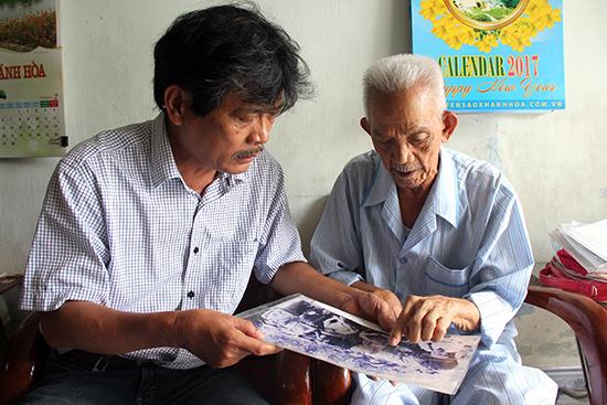 Ông Trần Ngọc Tuấn (phải) xem lại các kỷ vật liên quan đến tàu không số. Ảnh: Công Thi