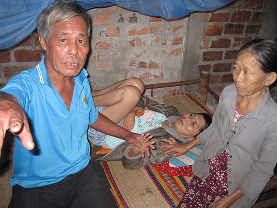 Vợ chồng ông Nguyễn Tấn Tiến chăm sóc người con bị tâm thần. Ảnh: B.L