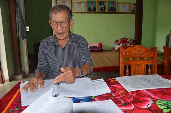 Ông Huỳnh Văn Nghiêm với đơn thư trình bày. Ảnh: T.N