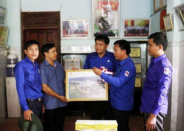 Bí thư Tỉnh đoàn Sê Kông Sakon Phonepaseuth (bên phải) tặng quà cho thanh niên Nguyễn Thanh Tuấn (xã Tam Hiệp, Núi Thành) khi đến thăm mô hình kinh tế. Ảnh: VINH