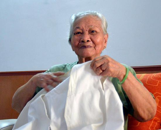 Bà Lê Thị Muộn trong một lần chụp ảnh cùng chiếc áo bà ba được may lại từ chiếc áo hải quân của con trai mình. Ảnh: XUÂN THỌ