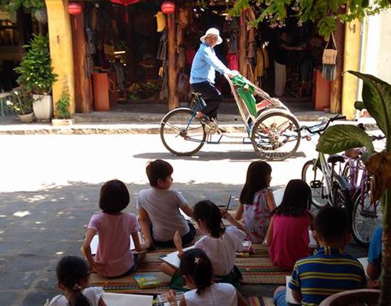 Các em thiếu nhi tại lớp mỹ thuật miễn phí của họa sĩ Trương Bách Tường thực hành sáng tác tại đường phố Hội An. Ảnh: T.N.N