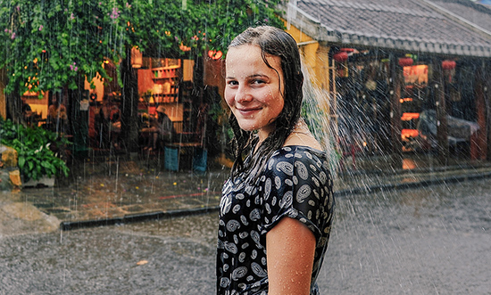 Trong cơn mưa, nụ cười hồn nhiên nở.
