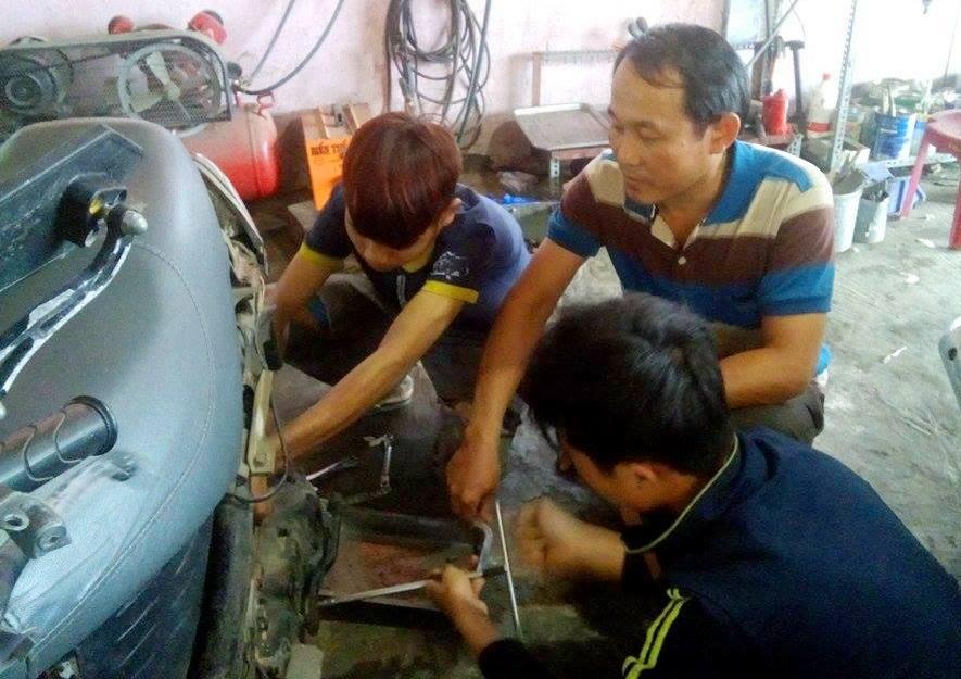 Anh Sơn bày vẽ cho các thanh niên trong tiệm sửa xe của mình.