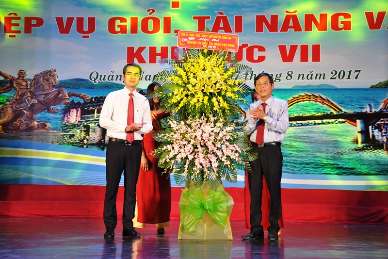 Ủ viên Ban Thường vụ Tỉnh ủy, Trưởng Ban Tuyên giáo Tỉnh ủy Nguyễn Chín (phải) tặng lẵng hoa chúc mừng hội thi. Ảnh: VINH ANH