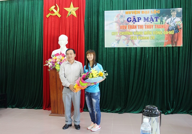 Bí thư Huyện ủy Phan Xuân Quang trao tặng hoa cho VĐV Thùy Trang. Ảnh: HOÀNG LIÊN