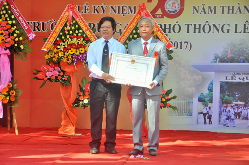 Thừa ủy nhiệm của Bộ trưởng Bộ GD-ĐT, lãnh đạo Sở GD-ĐT tặng bằng khen của Bộ GD-ĐT cho đại diện nhà trường. Ảnh: X.Phú