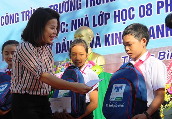 Đại diện nhà hảo tâm trao quà cho các em học sinh Trường THCS Phan Đình Phùng trong ngày khai giảng. Ảnh: ALĂNG NGƯỚC