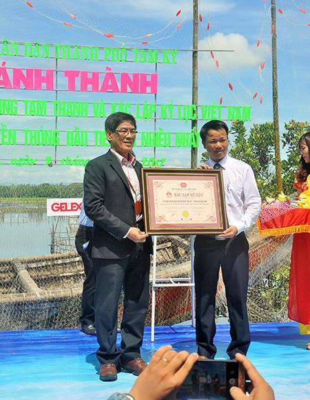 Ông Nguyễn Minh Nam (phải) đón nhận bằng kỷ lục con đường thuyền thúng đầu tiên và nhiều nhất Việt Nam. Ảnh: N.A