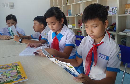Học sinh Trường Tiểu học Phan Ngọc Nhân say sưa đọc sách tại thư viện container. Ảnh: NHƯ TRANG
