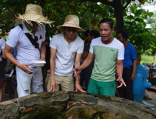 Võ Phúc Sinh (thứ nhất, bên phải) say sưa giới thiệu với du khách về giếng cổ ở đảo Cù Lao Chàm. Ảnh: N.Trang