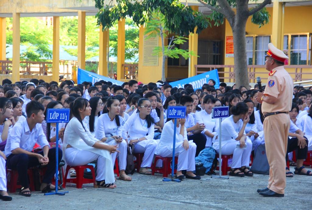Các em học sinh chăm chú lắng nghe các chiến sĩ CSGT tuyên truyền nhằm trang bị cho bản thân những kiến thức cần thiết về an toàn giao thông. Ảnh: ALĂNG NGƯỚC