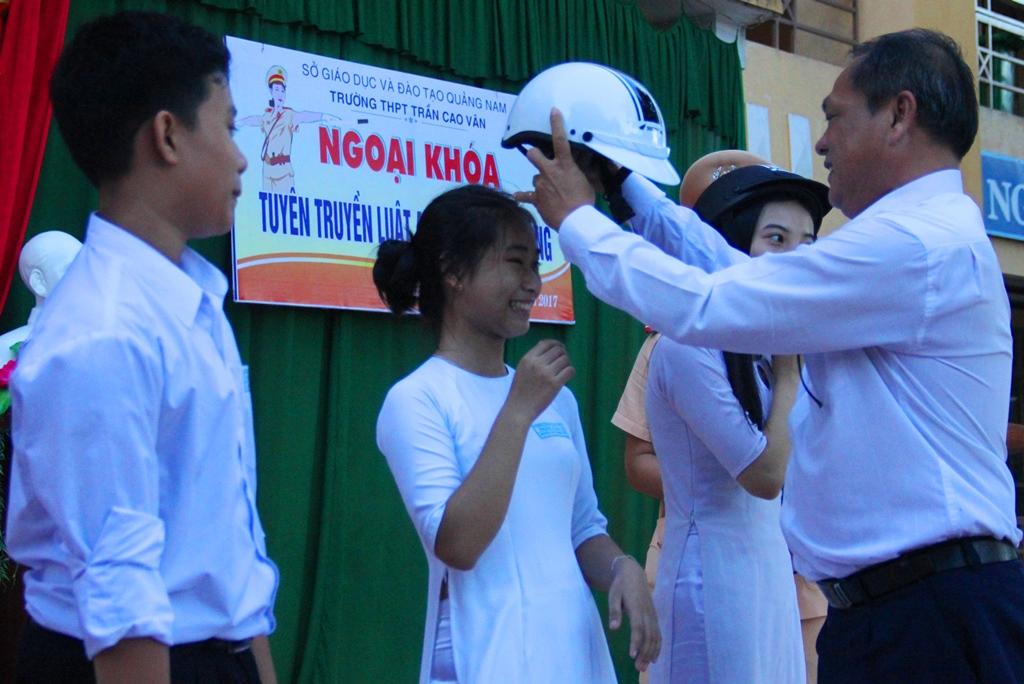 Đại diện lãnh đạo nhà trường trao phần thưởng mũ bảo hiểm cho các em học sinh trả lời chính xác câu hỏi đố vui tại buổi ngoại khóa. Ảnh: ALĂNG NGƯỚC