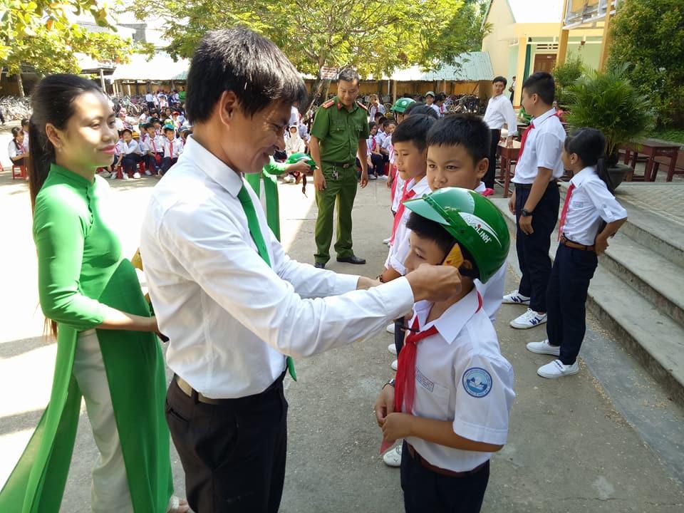 Trao mũ bảo hiểm do hãng taxi Mai Linh tài trợ cho học sinh phường Điện Dương. Ảnh: T.C