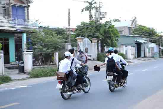 Học sinh không đội mũ bảo hiểm; riêng xe phân khối lớn còn chở 3, đùa giỡn trên đường.