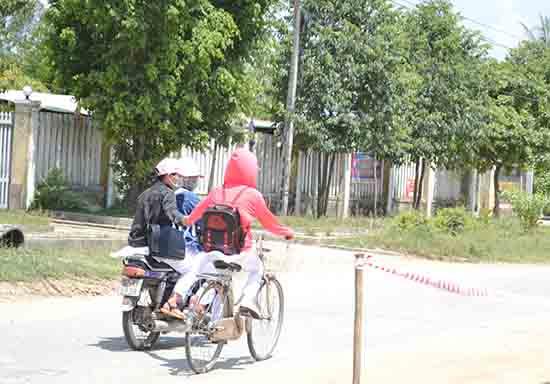 Nữ sinh đi xe phân khối lớn, không đội mũ bảo hiểm lại còn kéo theo bạn ngồi trên xe đạp.