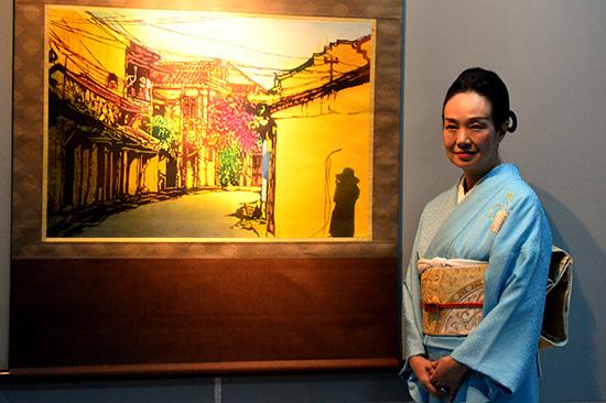 Bà Toba Mika chụp hình bên bức tranh về khung cảnh phố cổ Hội An (bức tranh duy nhất có hình bóng con người được bà vẽ tại Việt Nam).Ảnh: QUỐC TUẤN