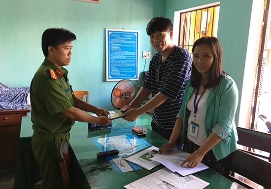 Thiếu tá Trương Đức Liên (trái) - Trưởng CA phường Minh An trả lại điện thoại bị mất cho du khách. Ảnh: CA phường Minh An cung cấp