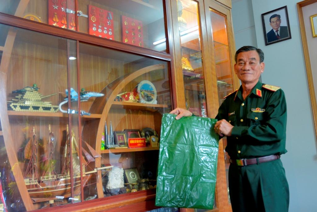Thiếu tướng Hoàng với chiếc túi nhựa để bảo vệ đồ đạc khỏi bị ướt khi vận chuyển từ tàu vào đảo Trường Sa. Ảnh: XUÂN THỌ