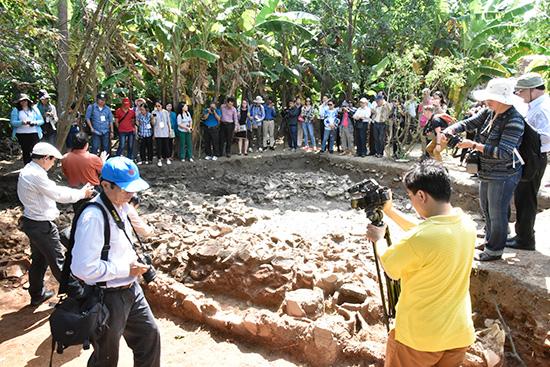 Các nhà khảo cổ tham quan điểm khai quật khảo cổ học về gốm Chăm. Ảnh: T.VỊNH