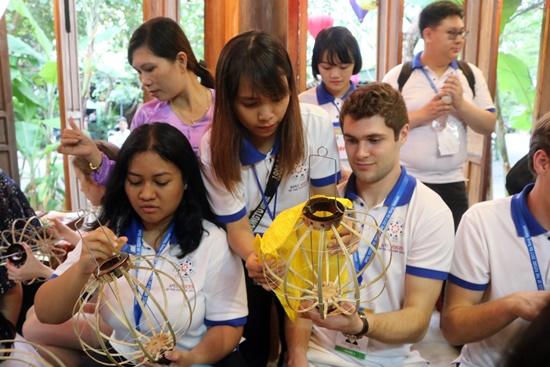 Các bạn trẻ đoàn Việt Nam hướng dẫn khách cách dán lồng đèn