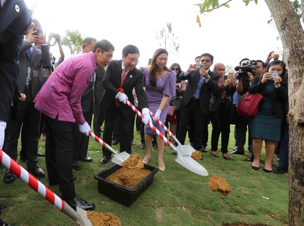Deputy Prime Minister Minh and other APEC delegates together planting a tree