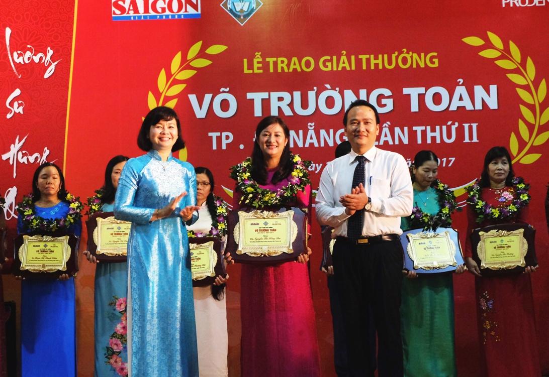 Bà Lý Việt Trung (áo dài xanh), Phó Tổng biên tập báo Sài Gòn Giải Phóng và ông Nguyễn Đình Vĩnh (áo trắng), Giám đốc Sở GD&ĐT TP Đà Nẵng trao giấy khen cho 20 thầy cô giáo tiêu biểu ở Đà Nẵng.