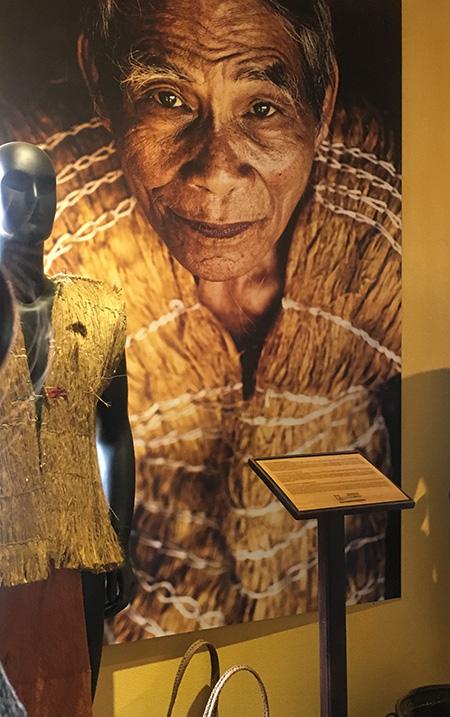 Bộ trang phục bằng vỏ cây của già làng Clâu Nâm và bức ảnh của ông ở bảo tàng Di sản vô giá. Ảnh: L.Q