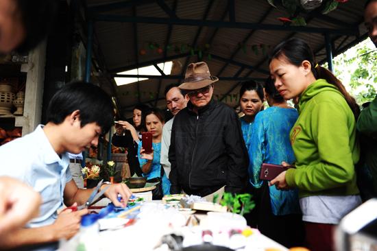 Các nghệ nhân làng gốm Thanh Hà xem 2 nghệ nhân trẻ của làng sản xuất hàng lưu niệm. Ảnh: MINH HẢI
