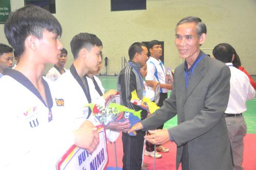Ông Bùi Rê-Giám đốc Trung tâm TD-TT tỉnh trao cờ và hoa động viên các đoàn tại lễ khai mạc. Ảnh: T.Vy