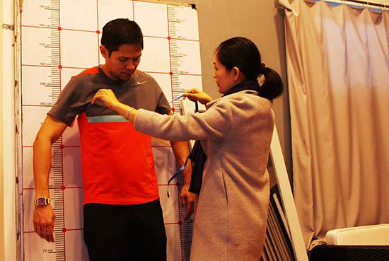 Nhân viên Công ty CP Thời trang Yaly lấy số đo để may nhanh quần áo cho khách du lịch. Ảnh: XUÂN THỌ