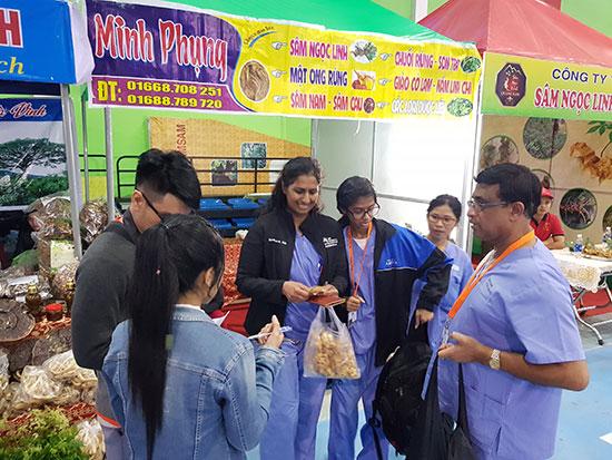 Du khách Mỹ tham quan gian hàng sâm Ngọc Linh tại phiên chợ.