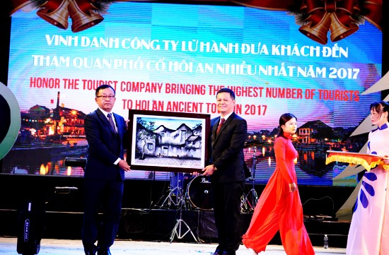 Chairman of the Hoi An city People's Committee Nguyen Van Dung (left) congratulated Saigontourists travel company bringing the 2.8 millionth international tourist to Hoi An in 2017