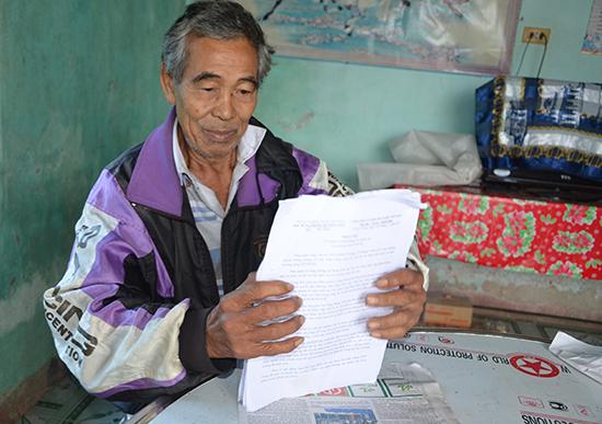 Ông Nguyễn Cúc với xấp hồ sơ giấy tờ đòi lại đất. Ảnh: T.H