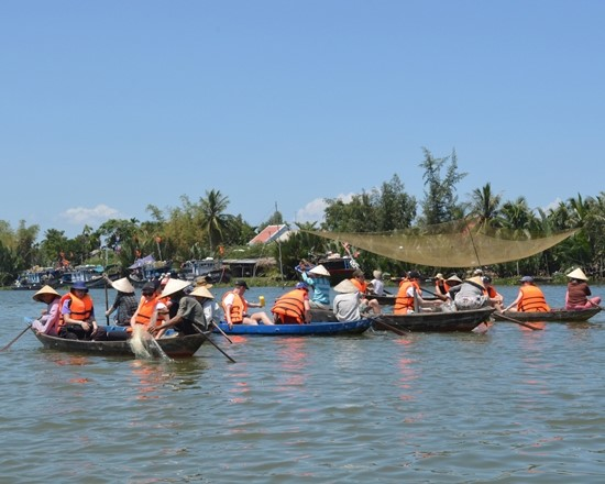 Visitors row boats in Tra Nhieu community-based tourism village