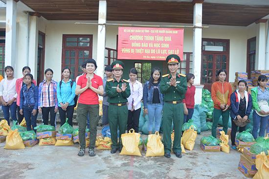 Tặng quà cho người dân bị thiệt hại do mưa lũ tại huyện Bắc Trà My. Ảnh: T.A