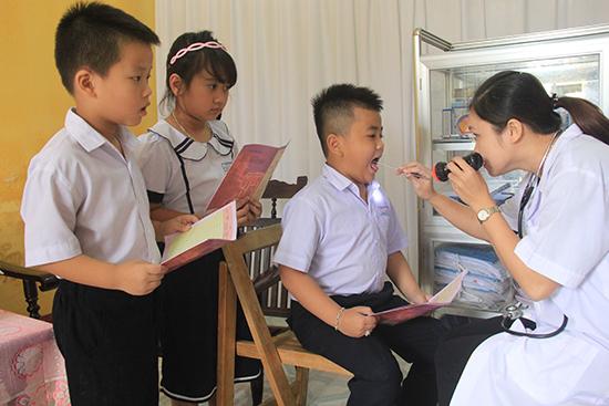 Hiện nay, y tế học đường nhiều nơi vẫn còn thiếu về số lượng và yếu về chất lượng.  Trong ảnh: Cán bộ y tế học đường kiểm tra sức khỏe học sinh  Trường Tiểu học Phan Thành Tài - Điện Bàn.Ảnh: DƯƠNG HIỀN