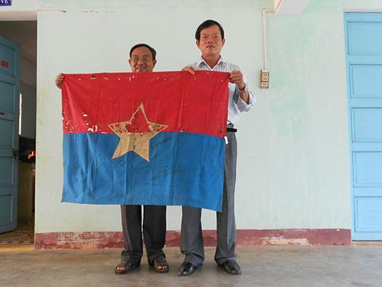 Tác giả (bên trái) trao lá cờ Mặt trận Dân tộc giải phóng miền Nam Việt Nam nhân dân Kỳ Anh sử dụng trong cuộc nổi dậy xuân Mậu Thân cho ông Nguyễn Nay - Giám đốc Bảo tàng tỉnh.