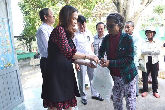 Vợ ông Phan Ngọc Anh trao tặng quà cho gia đình bệnh nhân ngoại trú. Ảnh: CT