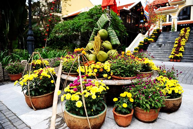 Phần gốc của cây nêu được trang trí hoa tươi bắt mắt, nhưng không thể tgieeus các món bánh truyền thống của ngày tết như bánh tét, bánh chưng, hay quả dừa.... Ảnh: MINH HẢI
