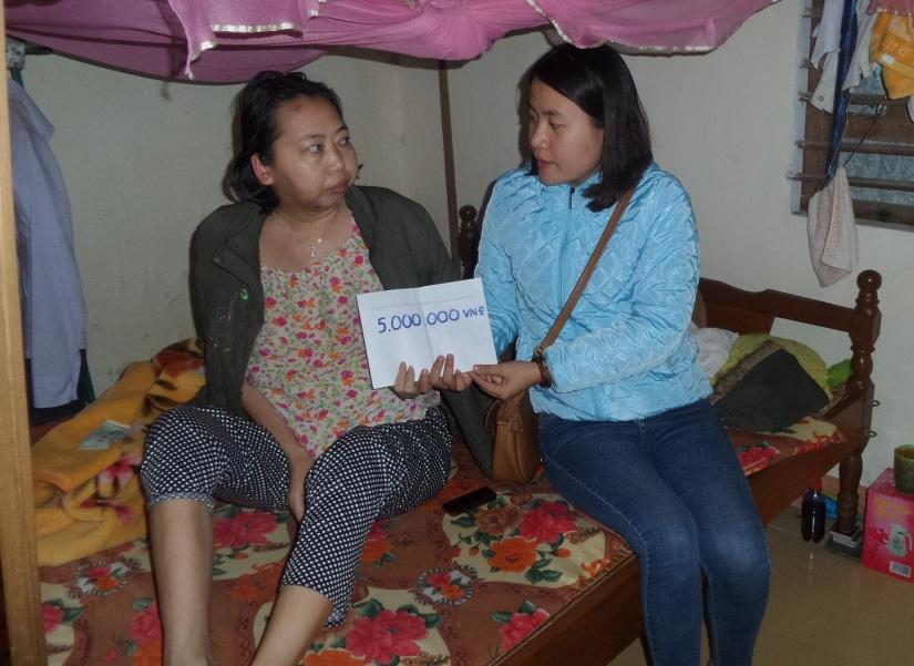 Chị Trịnh Thị Trâm Oanh nhận tiền các nhà hảo tâm giúp đỡ. (ảnh: Như Trang)
