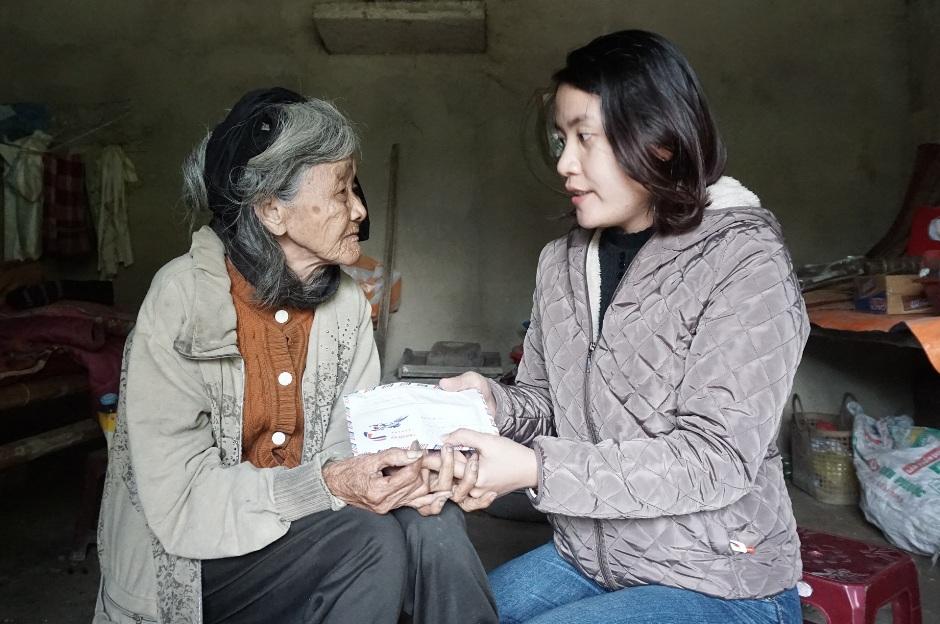 Cụ Nguyễn Thị Thoàn nhận tiền các nhà hảo tâm giúp đỡ. (ảnh: Như Trang)