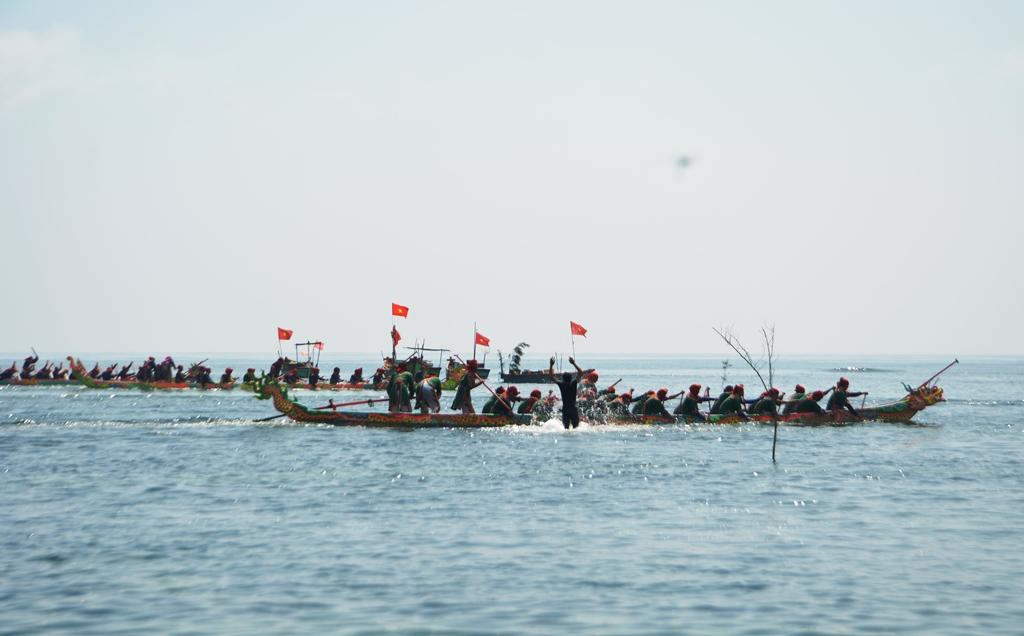 Để cổ vũ cho đội thuyền xóm mình, có người lội nước ra tận đường đua. Ảnh: XUÂN THỌ
