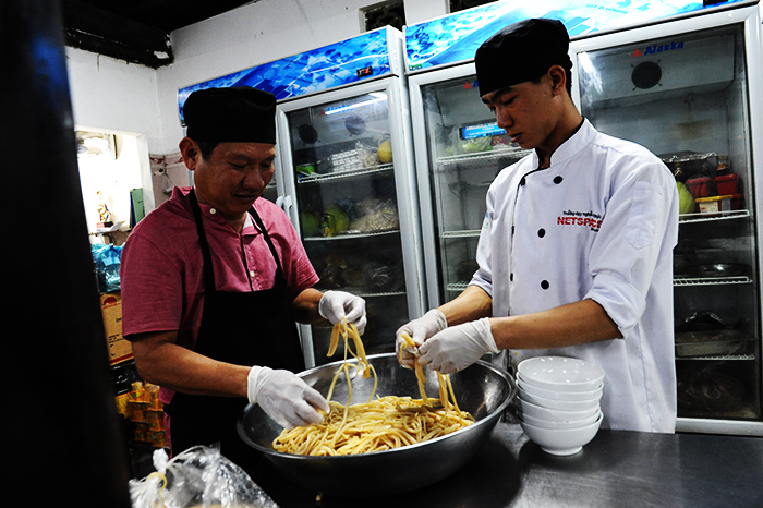 Making cao lau-a regional Vietnamese dish made of noodles, pork, and local greens. It is popular and famous in Hoi An city