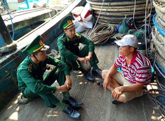 Các cán bộ, chiến sĩ Đồn Biên phòng cửa khẩu cảng Kỳ Hà tuyên truyền cho ngư dân trước mỗi chuyến ra khơi. Ảnh: ALĂNG NGƯỚC