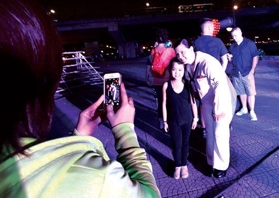 Tranh thủ giờ chuẩn bị, bé Trần Chân Thiện Mỹ (10 tuổi), phường Mỹ An, quận Ngũ Hành Sơn, được mẹ chụp ảnh cùng giọng ca chính Emile.