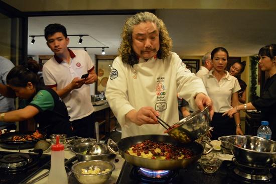 Đầu bếp Trung Quốc đang chế biến món ăn đại diện cho dân tộc mình để giới thiệu đến khách
