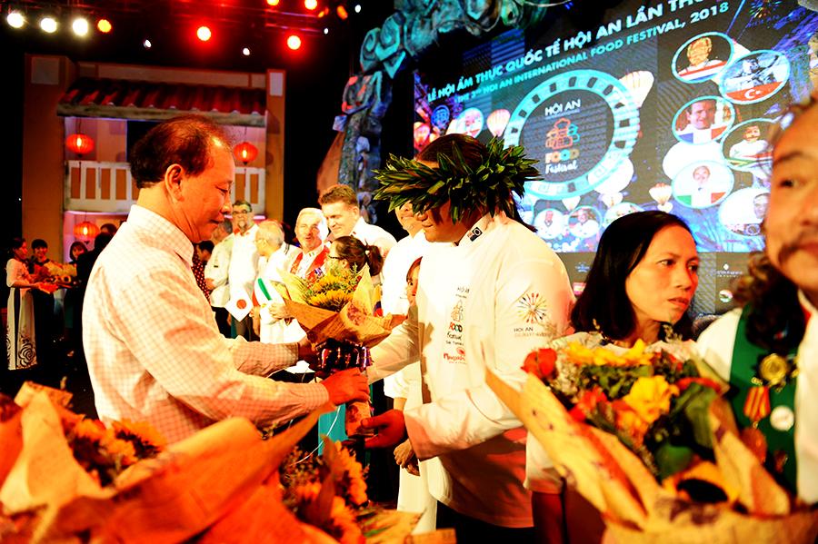 Lãnh đạo TP.Hội An tặng hoa cho các đầu bép tham dự liên hoan. Ảnh: HẢI - LỘC
